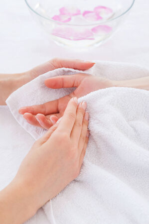 Beauty treatment. Close-up of beautician drying customers hand with towel  photo