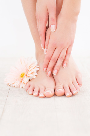 Keeping her feet clean and smooth. Close-up of woman touching her feet while standing on hardwood floor photo