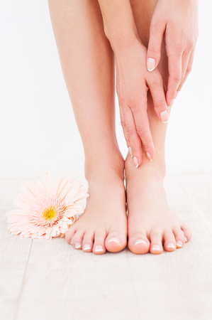 Taking care of her feet. Close-up of young woman touching her feet while standing on hardwood floor photo