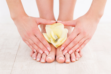 manicure and pedicure: Beautiful manicure and pedicure. Close-up of young woman touching her feet while standing on hardwood floor Stock Photo