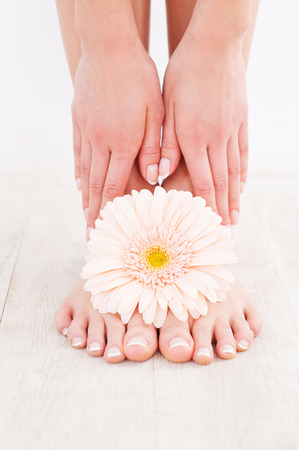Beautiful feet. Close-up of young woman touching her feet while standing on hardwood floor photo