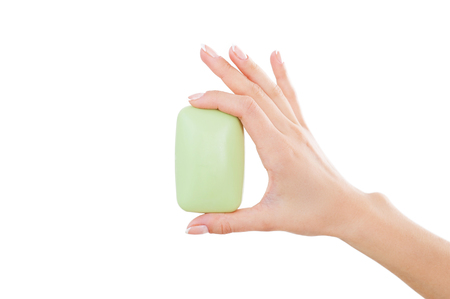 Soap bar. Close-up of woman holding soap bar while isolated on white photo