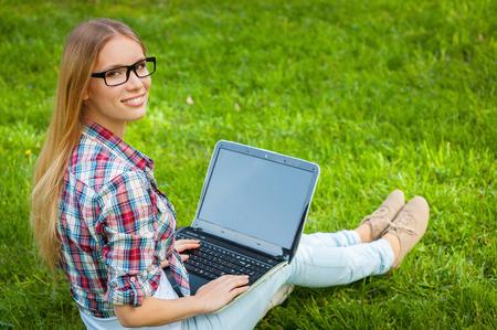 Surfen im Netz in der Natur. Schöne junge Studentin arbeitet am Laptop und Blick über die Schulter, während sitzen auf dem Rasen im Park