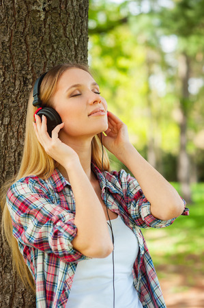 Enjoying music and fresh air. Side view of beautiful young woman in headphones listening to the music and smiling while leaning at the tree in a park