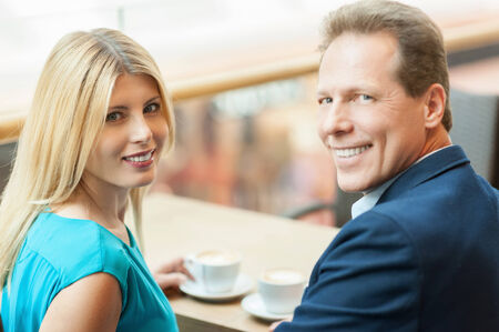 Drinking coffee together. Beautiful mature couple drinking coffee together and looking at camera while sitting in coffee shop photo