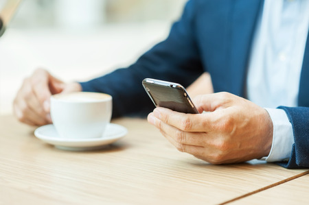 Always in touch. Cropped image of man in formalwear drinking coffee and typing a message on mobile phone while sitting in restaurant photo