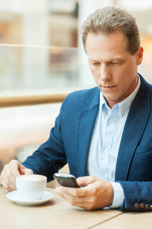 Taking time for coffee break. Confident mature man in formalwear drinking coffee and typing a message on mobile phone while sitting in restaurant photo