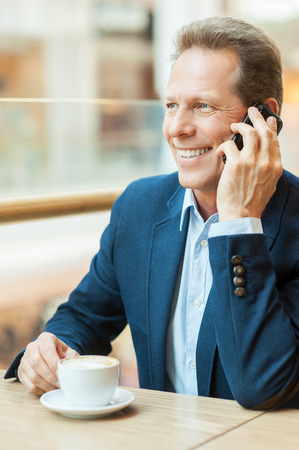 Staying connected. Confident mature man in formalwear drinking coffee and talking on mobile phone while sitting in restaurant photo