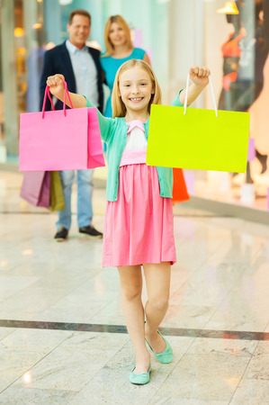 spending full: Family shopping. Cheerful family shopping in shopping mall while little girl showing her shopping bags and smiling Stock Photo