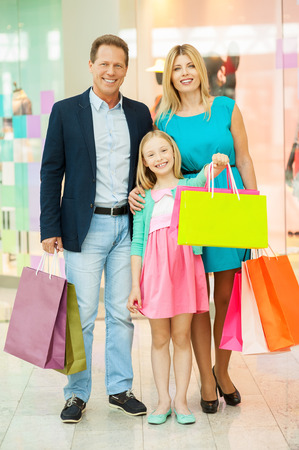 Family in shopping mall. Full length of cheerful family holding shopping bags and smiling while standing in shopping mall photo