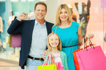 Gelukkig gezin winkelen. Vrolijke familie bedrijf boodschappentassen en glimlachend in de camera terwijl in winkelcentrum