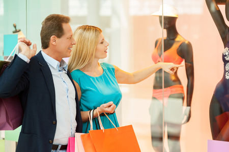 I want this! Cheerful mature couple shopping in shopping mall while woman pointing mannequin  Stok Fotoğraf