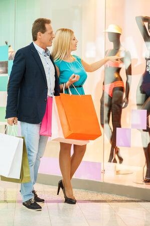 Just look at that! Full length of cheerful mature couple shopping in shopping mall while woman pointing mannequin  photo