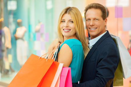 Couple shopping. Cheerful mature couple holding shopping bags and looking over shoulder while standing in shopping mall  photo