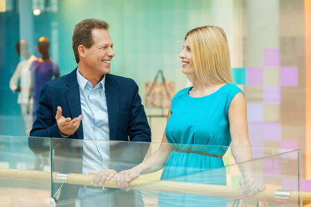 Couple in shopping mall. Cheerful mature couple talking to each other while standing in shopping mall  photo