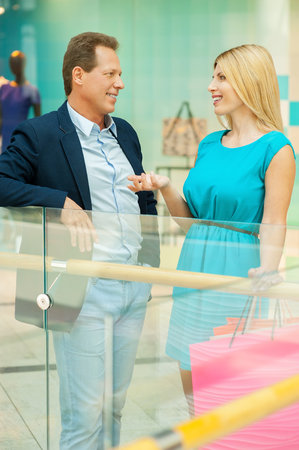 Spending time in shopping mall. Cheerful mature couple talking to each other and gesturing while standing in shopping mall  photo