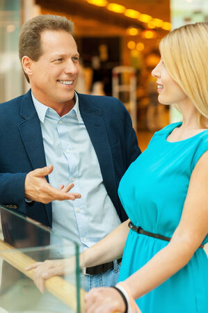 Couple in shopping mall. Beautiful mature couple talking to each other while standing in shopping mall  photo