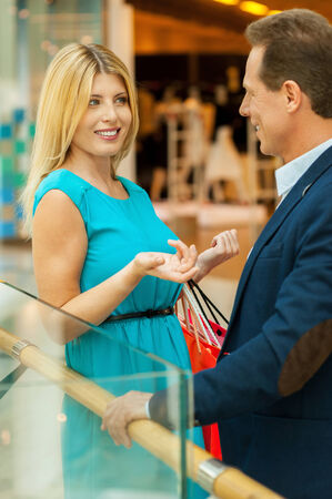 Discussing sale. Beautiful mature couple talking to each other while standing in shopping mall  photo