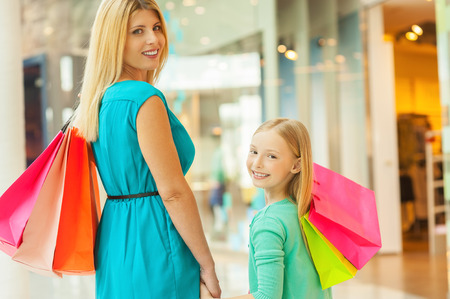 We love shopping together! Cheerful blond hair mother and daughter holding shopping bags and looking over shoulder while standing in shopping mall