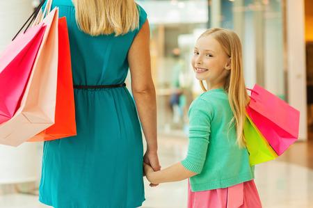 Little shopaholic. Achter mening van moeder en dochter met boodschappentassen terwijl meisje kijkt over de schouder en glimlachend Stockfoto