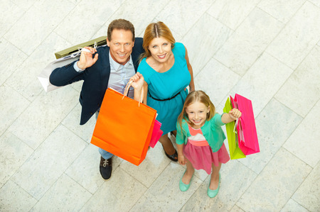 We love shopping! Top view of cheerful family holding shopping bags and smiling at camera while standing in shopping mall photo