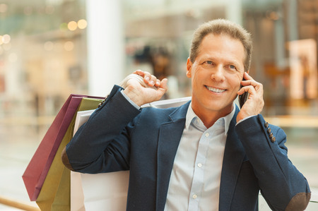 Man in shopping mall. Confident mature man holding shopping bags and talking on the mobile phone while standing in shopping mall photo