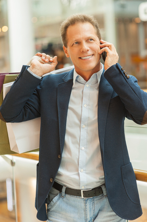 only men: Man shopping. Cheerful mature man holding shopping bags and talking on the mobile phone while standing in shopping mall