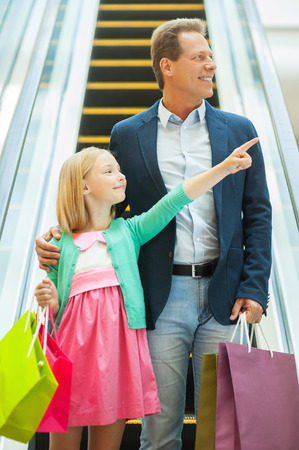 Father and daughter shopping. Cheerful father and daughter moving down by escalator and holding shopping bags photo