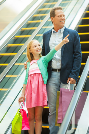 Look over there! Cheerful father and daughter moving down by escalator while little girl holding shopping bags and pointing away photo