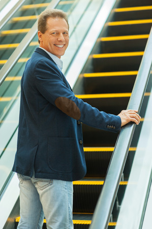 I am going up. Cheerful mature man looking over shoulder and smiling while moving up by escalator photo