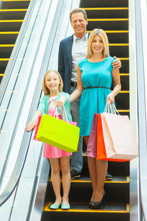 Family on shopping spree. Cheerful family holding shopping bags and smiling at camera while moving by escalator photo