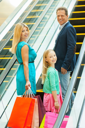 Shopping together is fun! Cheerful family holding shopping bags and looking over shoulder while moving up by escalator photo