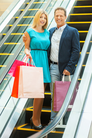 We love shopping together! Full length of cheerful mature couple holding shopping bags and smiling while moving by escalator  photo