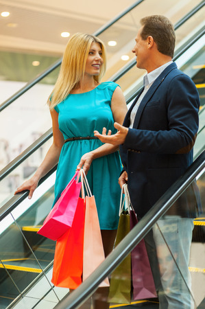 Couple shopping. Cheerful mature couple holding shopping bags and talking to each other while moving by escalator  photo