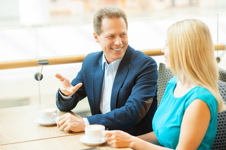 Relaxing in cafe together. Beautiful mature couple drinking coffee and talking to each other while sitting in coffee shop photo
