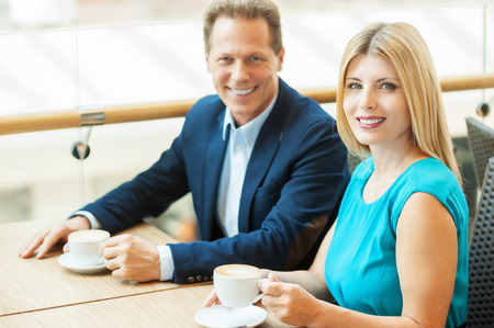 Spending time together. Beautiful mature couple drinking coffee together and looking at camera while sitting in coffee shop photo