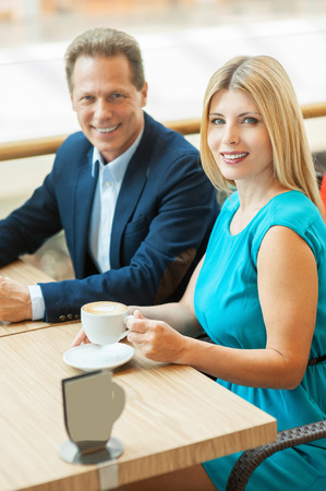 Couple in coffee shop. Top view of beautiful mature couple drinking coffee together and looking at camera while sitting in coffee shop photo