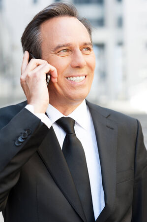 Business talk. Confident senior man in formalwear talking on the mobile phone and smiling while standing outdoors photo