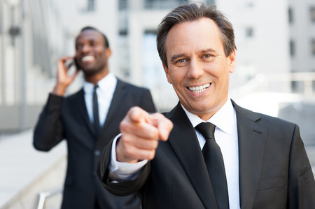 I choose you! Confident senior man in formalwear pointing you and smiling while African man talking on the mobile phone in the background   photo