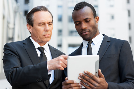 Consulting with expert. Two confident business men looking at the digital tablet while one of them pointing it with finger photo