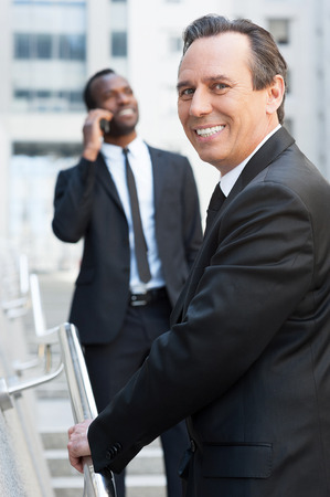 He is the best in his business. Cheerful senior man in formalwear moving up by stairs and looking over shoulder while African man talking on the mobile phone in background   photo