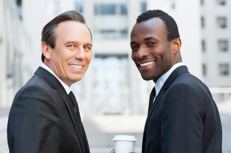 looking over shoulder: The best of business world. Two confident business men looking over shoulder and smiling while standing outdoors