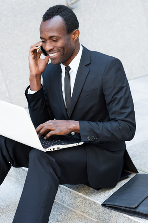 Successful businessman. Happy young African man in formalwear talking on the mobile phone and working on laptop while sitting on outdoors staircase photo
