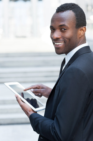 over the shoulder view: Working on tablet. Cheerful young African man in formalwear working on digital tablet and looking over shoulder while standing outdoors