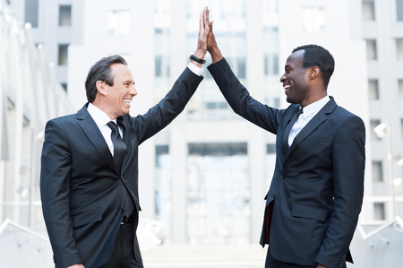 Business winners. Two cheerful business men clapping each other hands and smiling while standing outdoors
