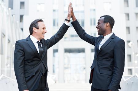 manos aplaudiendo: Ganadores de Negocios. Dos hombres de negocios alegres que aplauden las manos entre sí y sonriendo mientras está de pie al aire libre