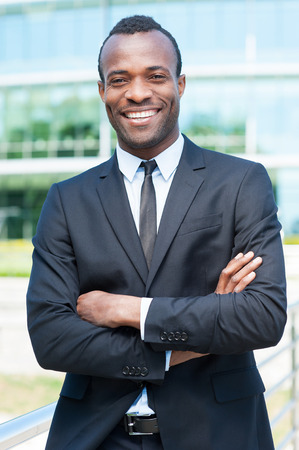 man only: Confident and successful businessman. Handsome young African man in full suit keeping arms crossed and looking at camera while standing outdoors
