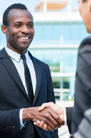 Business people shaking hands. Two business men shaking hands and smiling while standing outdoors photo