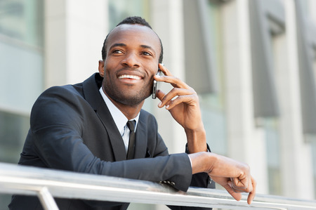 black businessman: Good business talk. Happy young African man in formalwear talking on the mobile phone and smiling while standing outdoors