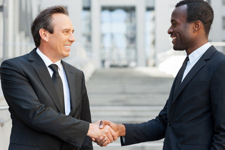 of african descent: Business handshake. Two cheerful business men shaking hands while standing outdoors
